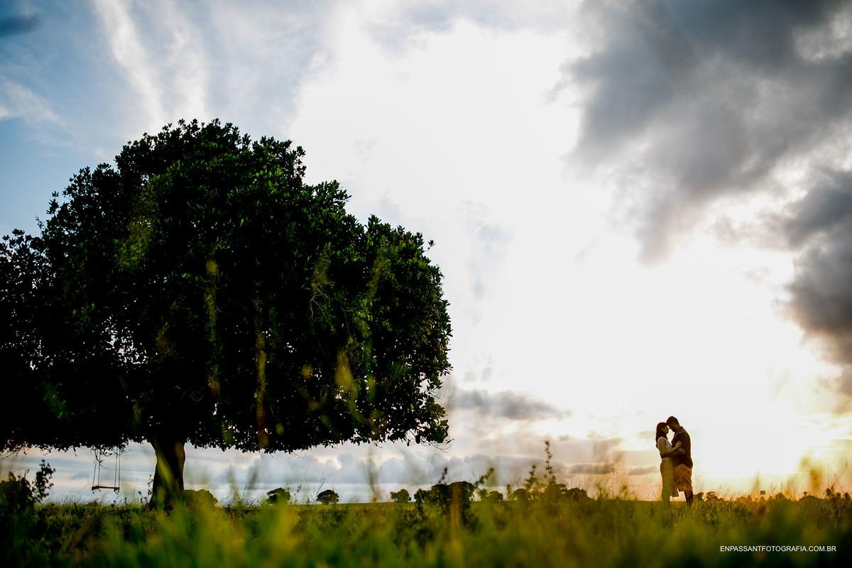 casal abraçado perto de árvore