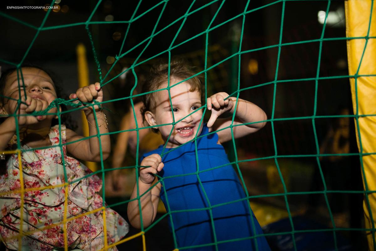 criança agarrada na rede do pula pula