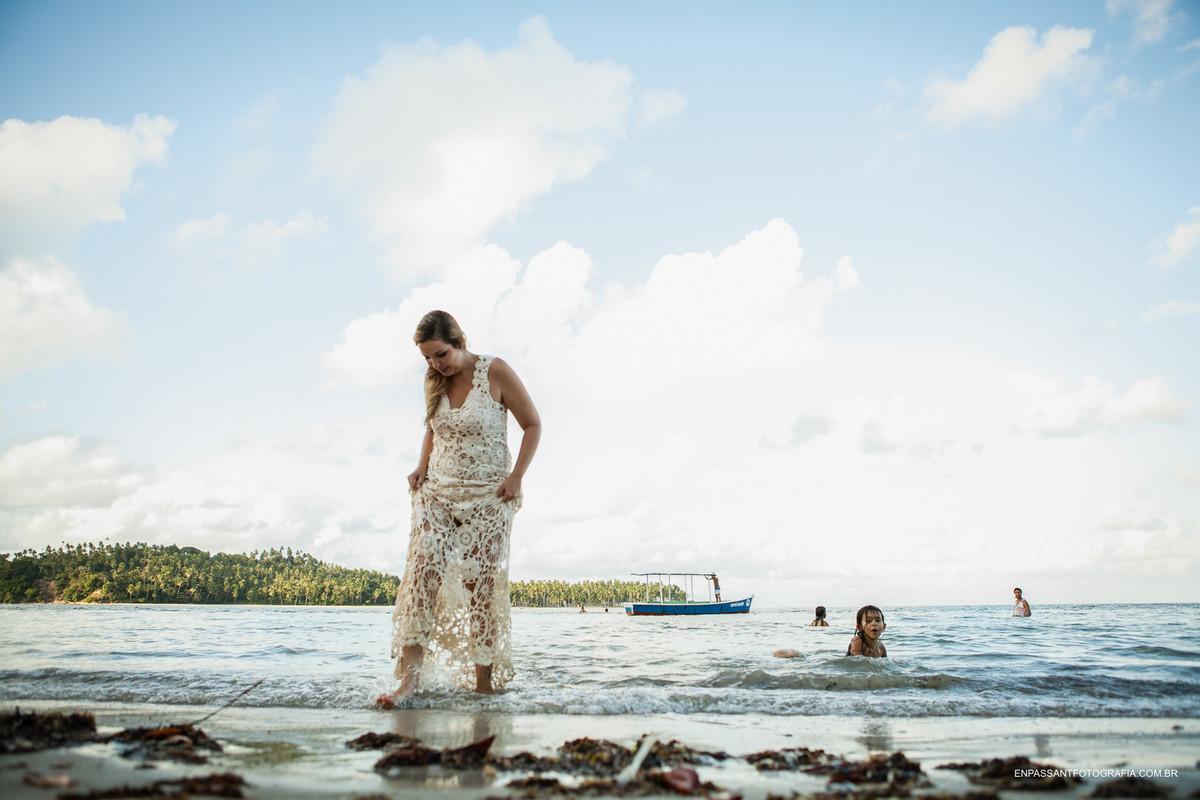 menina olha noiva saindo do mar