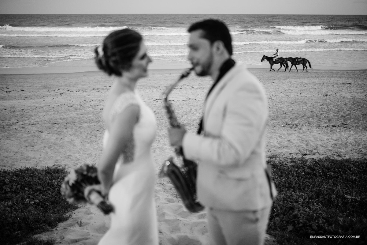 noivo toca sax para noiva na beira da praia