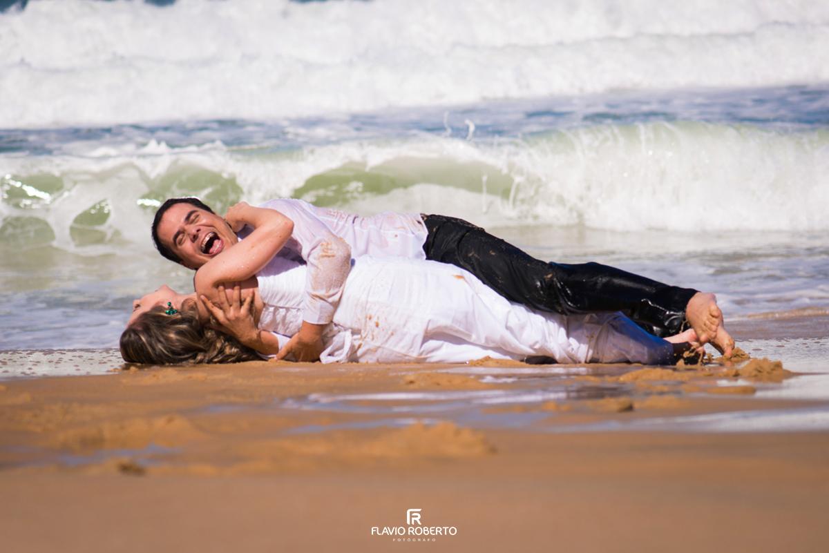 noiva rolando com o noivo na areia da praia