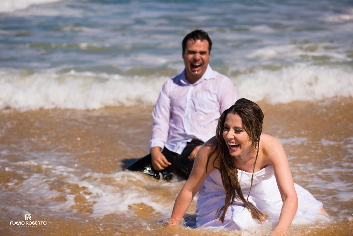 noivos rindo no trash the dress na praia