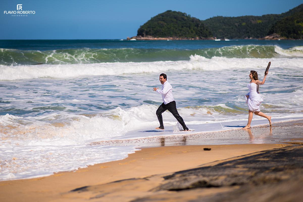 Noiva correndo atrás do Noivo na praia
