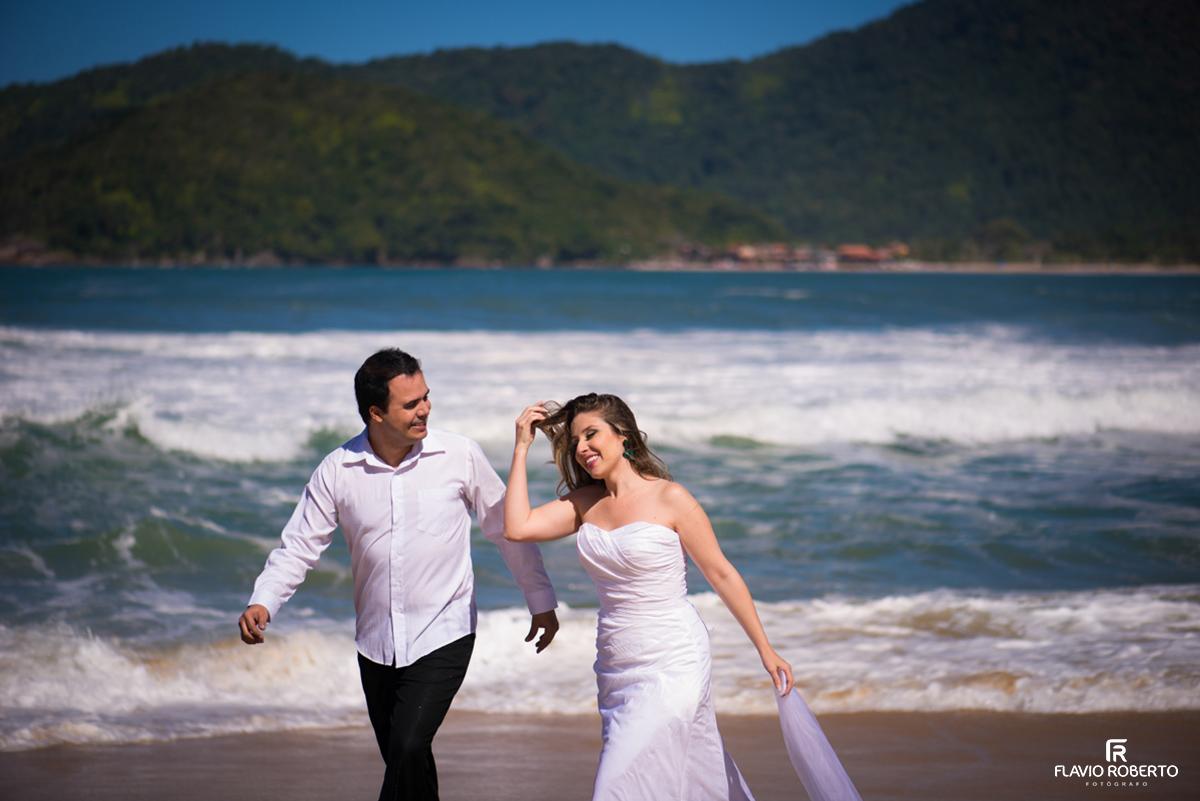 recém casados caminhando na praia