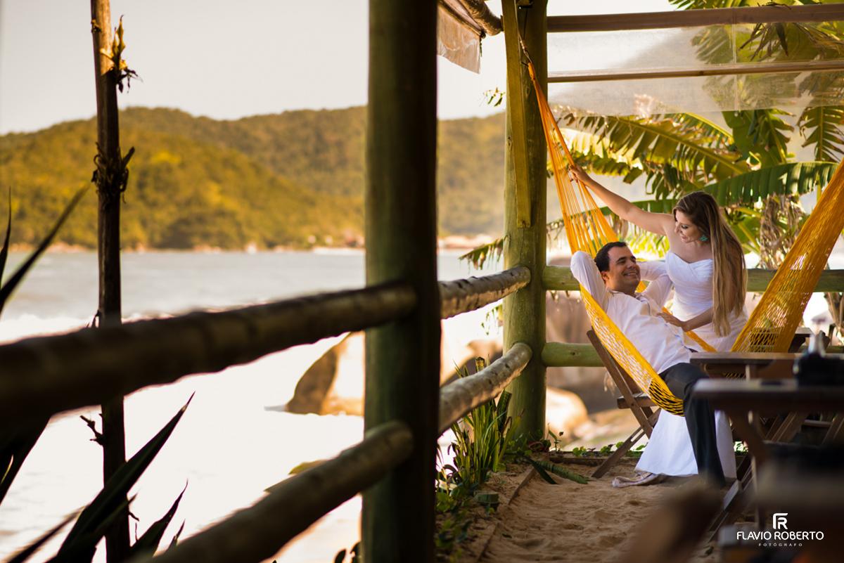 Casal deitando na rede la beira da praia