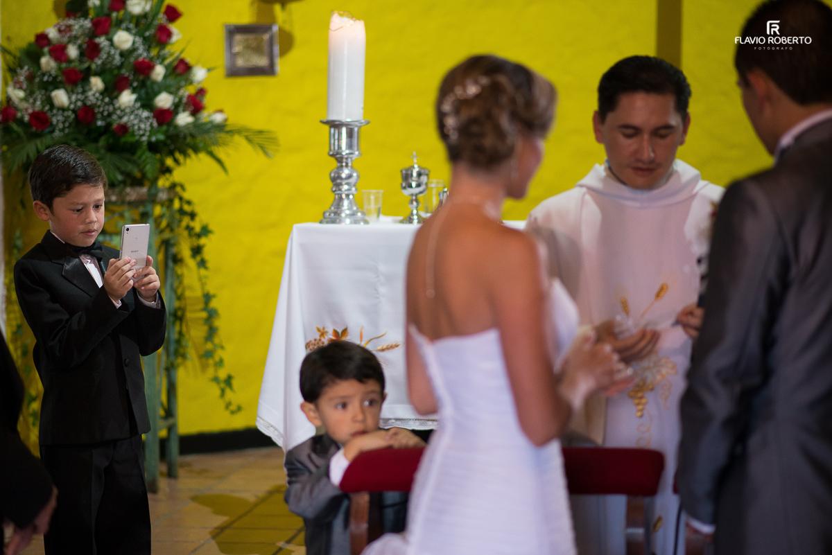 criança fotografando os noivos na cerimonia de casamento