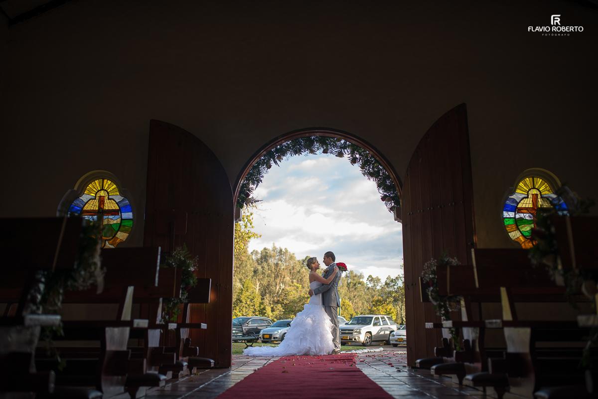noivos se abraçando em frente a capela onde se casaram