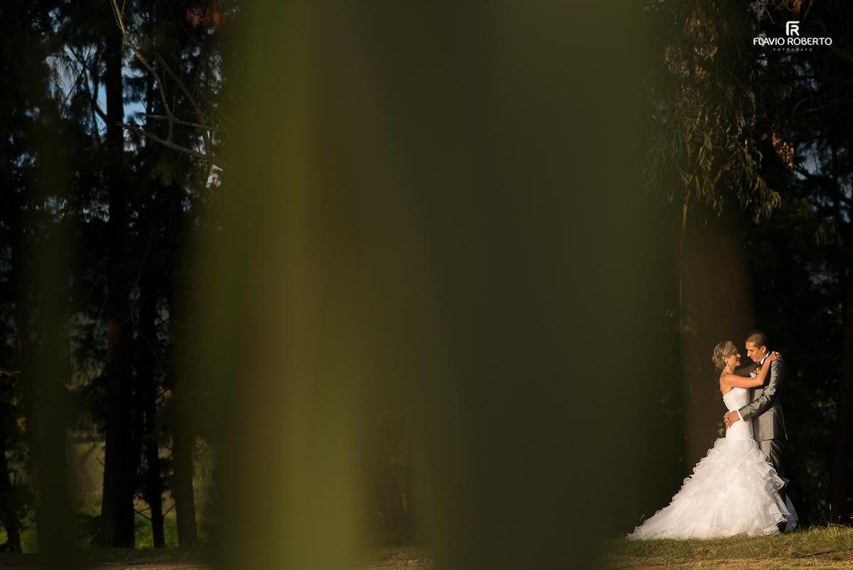 casal de noivos se abraçando em um dia lindo