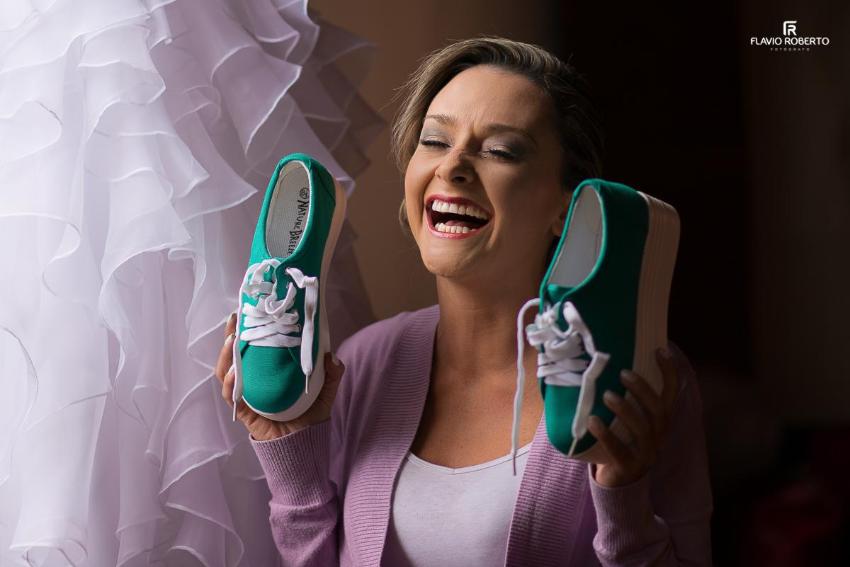 noiva divertida segurando seus sapatos verdes