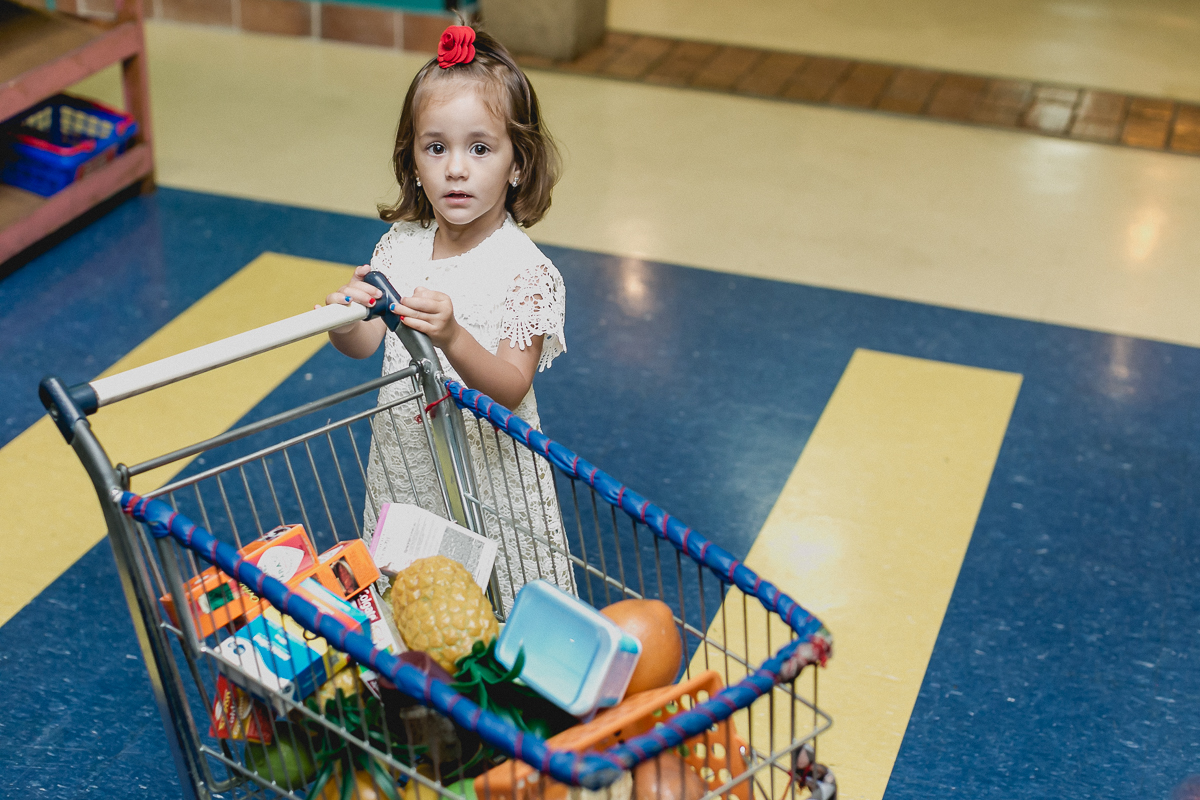 Sofia fazendo compras no mercadinho do buffet miniland