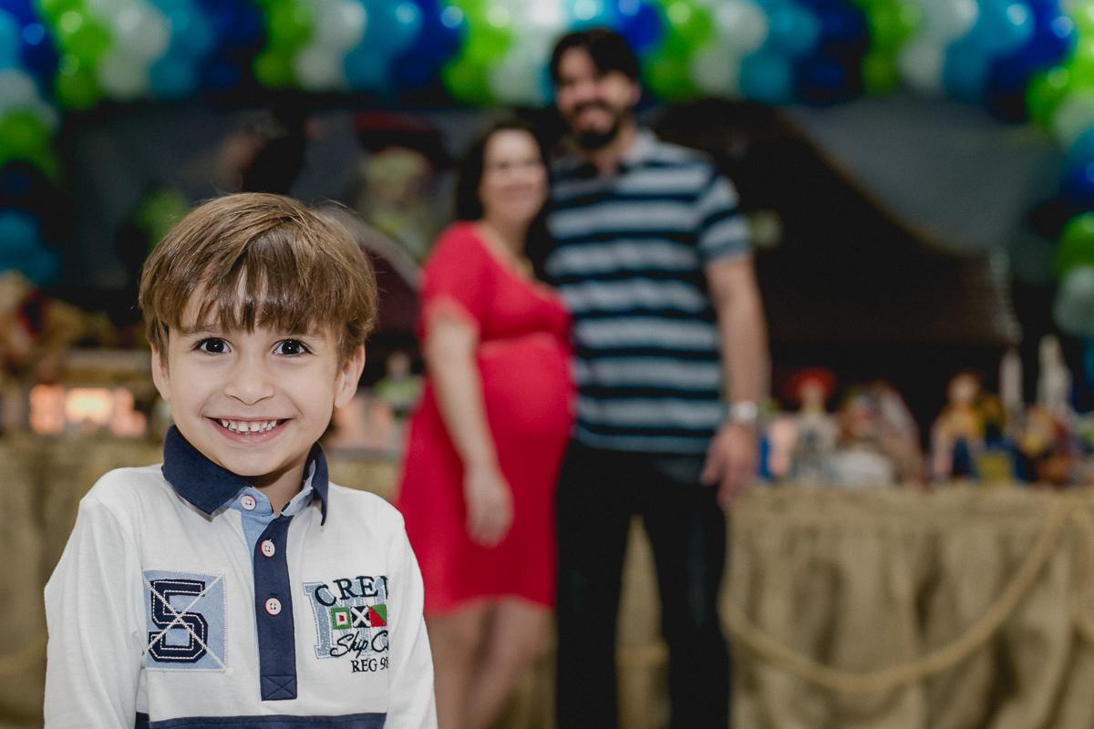 Pedro na frente da mesa do bolo com o papai e a mamae