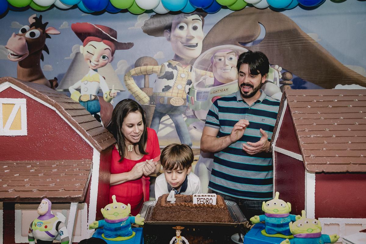 Pedro e familia assoprando a vela na hora do parabens