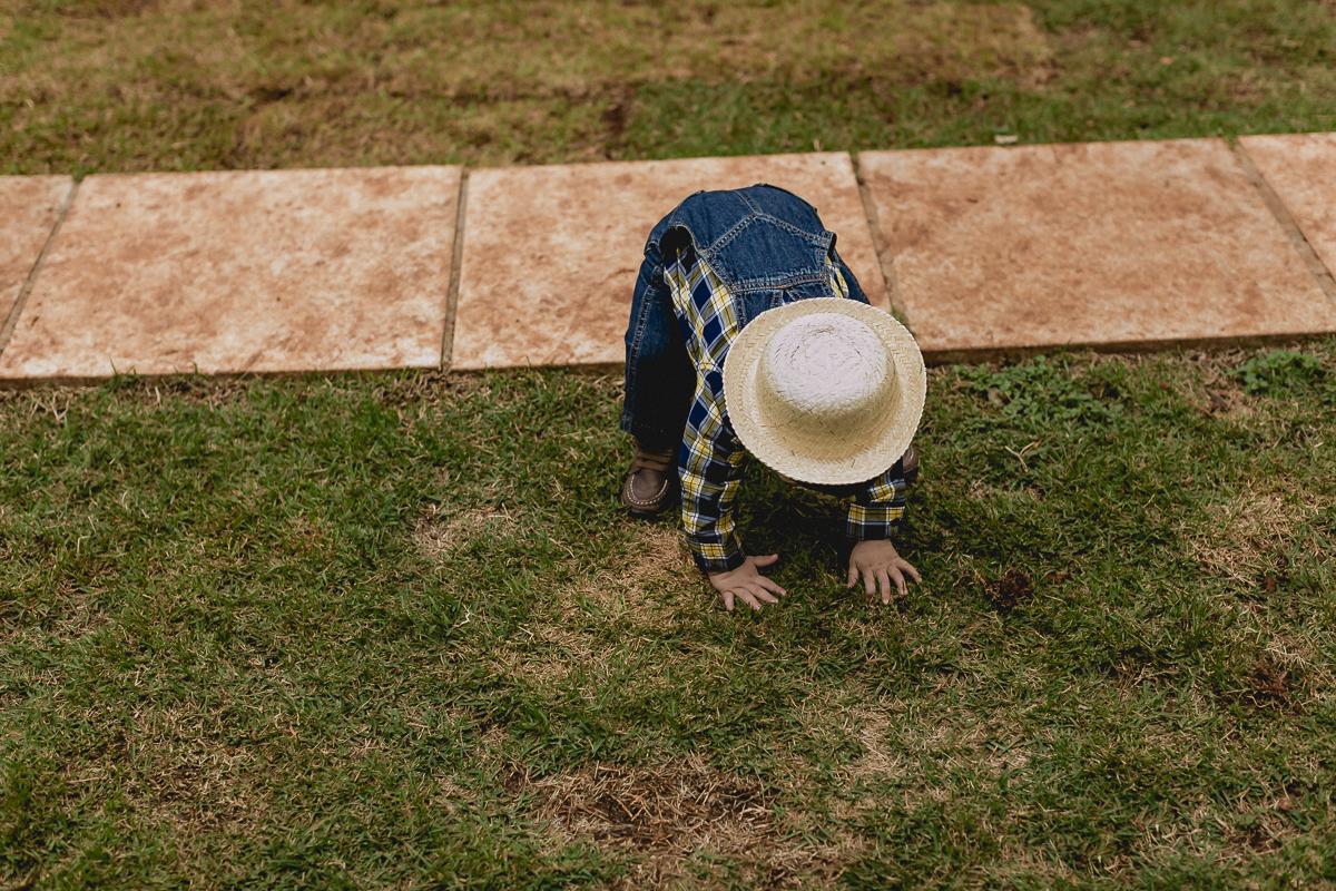 de chapeu agachando no chão
