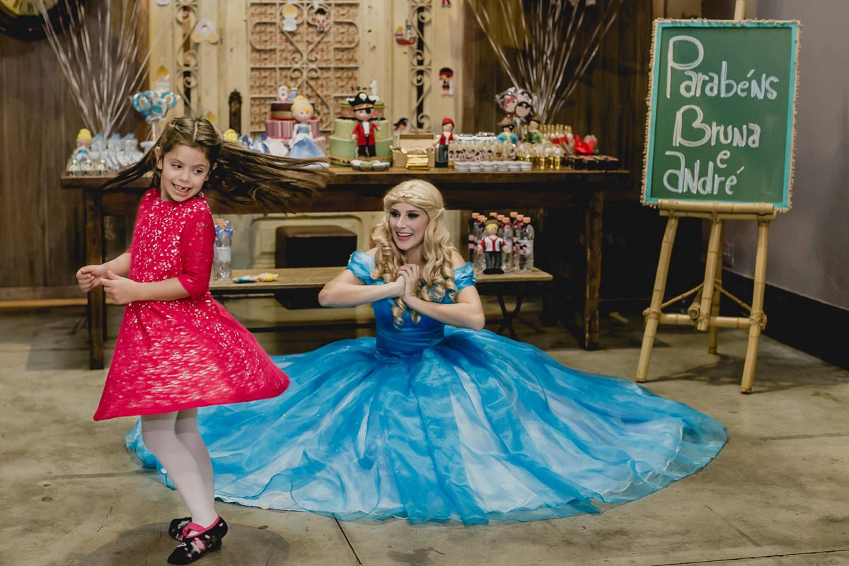 Bruna girando e balancando o vestido com a princesa na frente da mesa