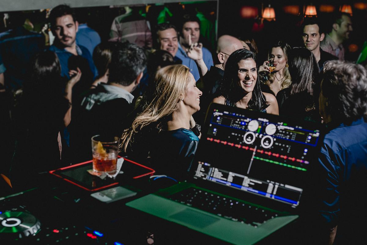 Mesa do DJ e Clarissa e amigos ao fundo curtindo a festa
