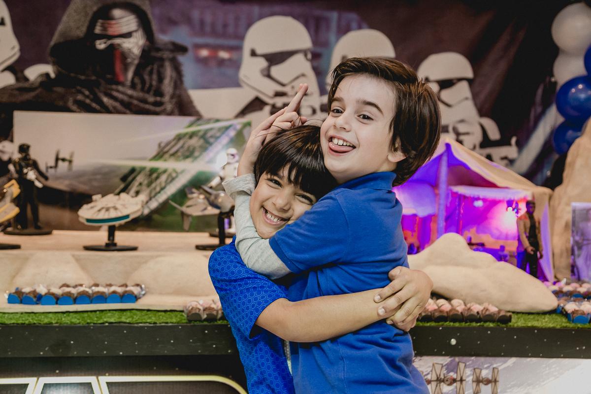 amigos se abraçando na frente da mesa do staw wars