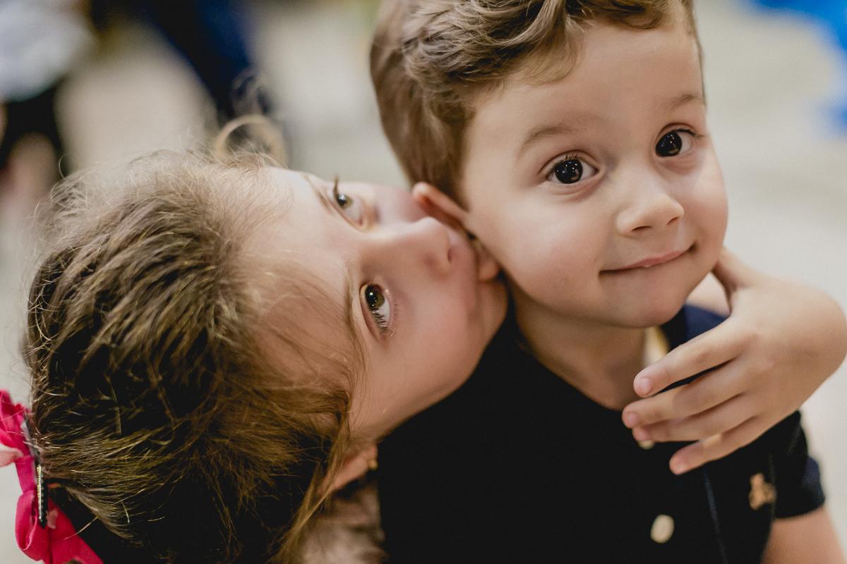 irmã beijando a orelha do irmão