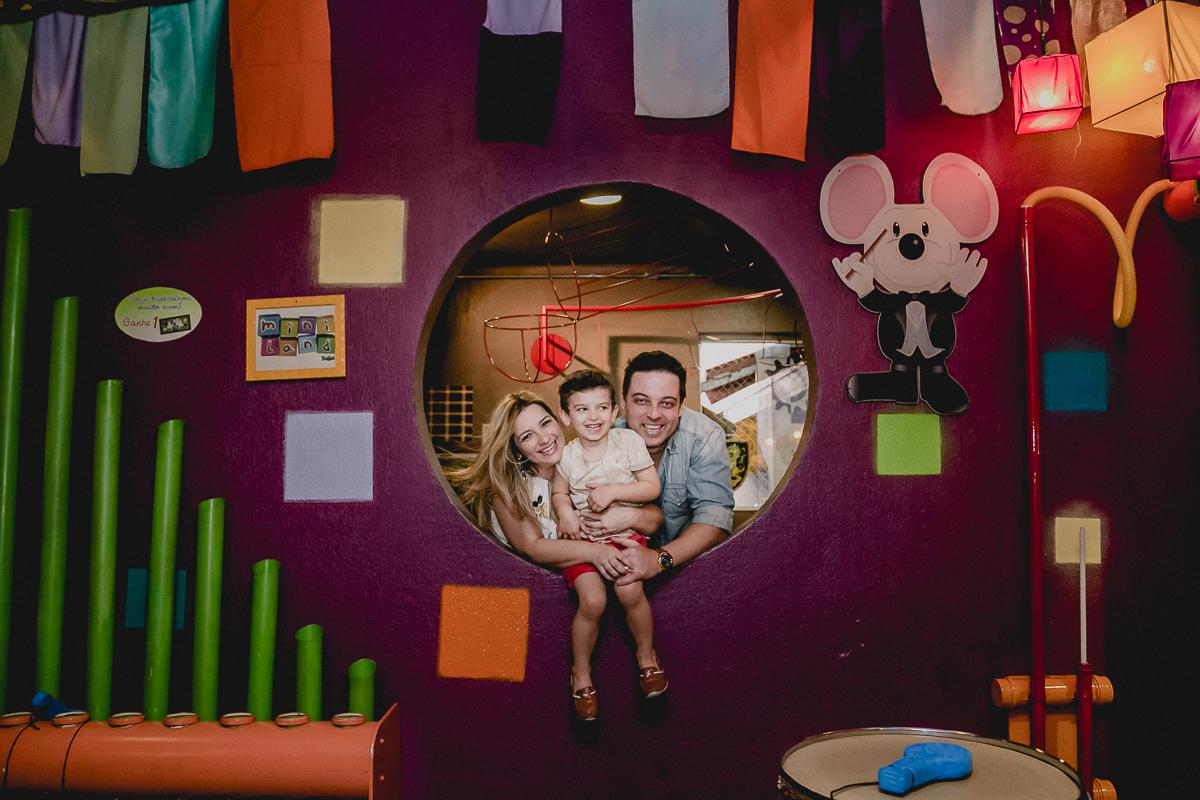 theo, mamãe e papai no buraco da parede no brinquedo do buffet miniland