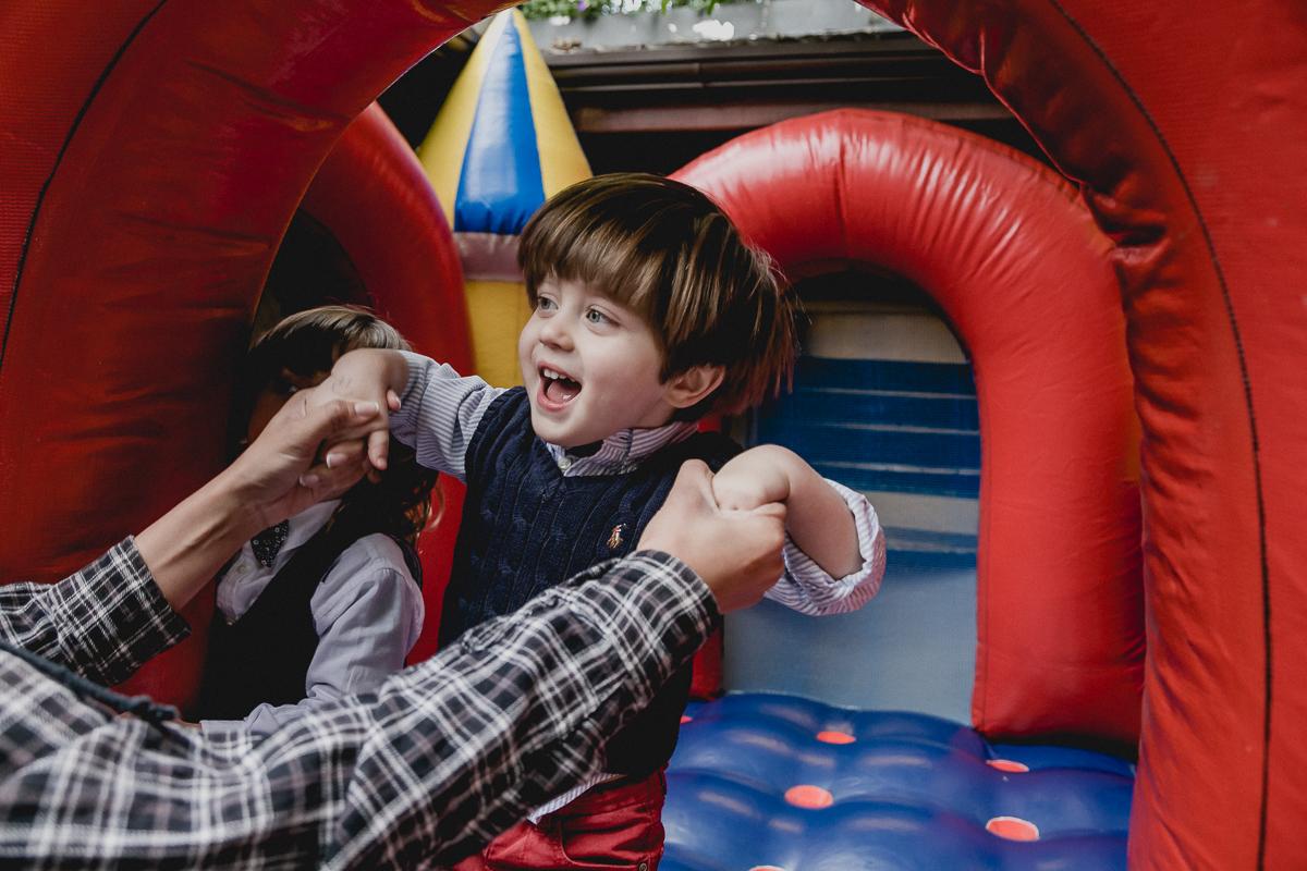 sorrindo muito e pulando no brinquedo inflavel