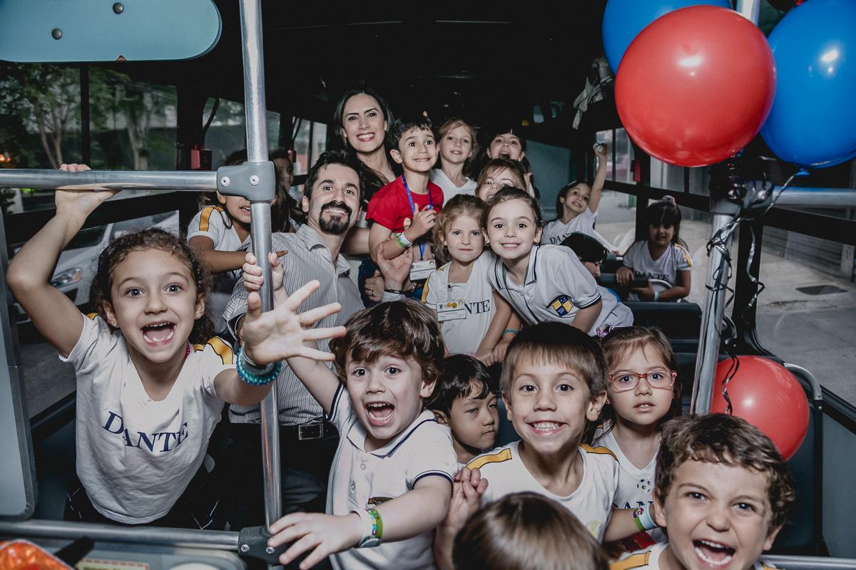 crianças dentro do onibus ansiosas para entrar na festa