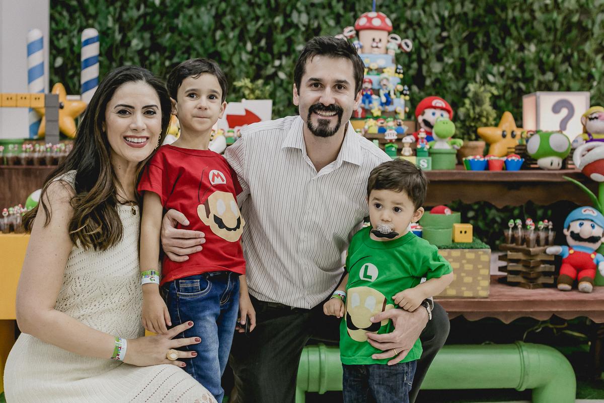 fotografia de familia na frente da mesa do bolo