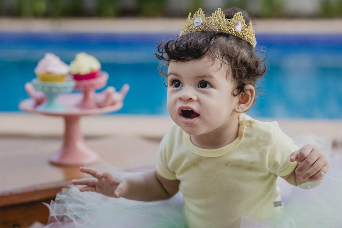 lia com sua coroa sorrindo no smash the cake