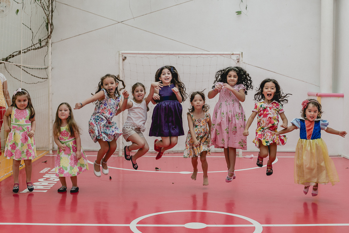 crianças brincando de pular na quadra