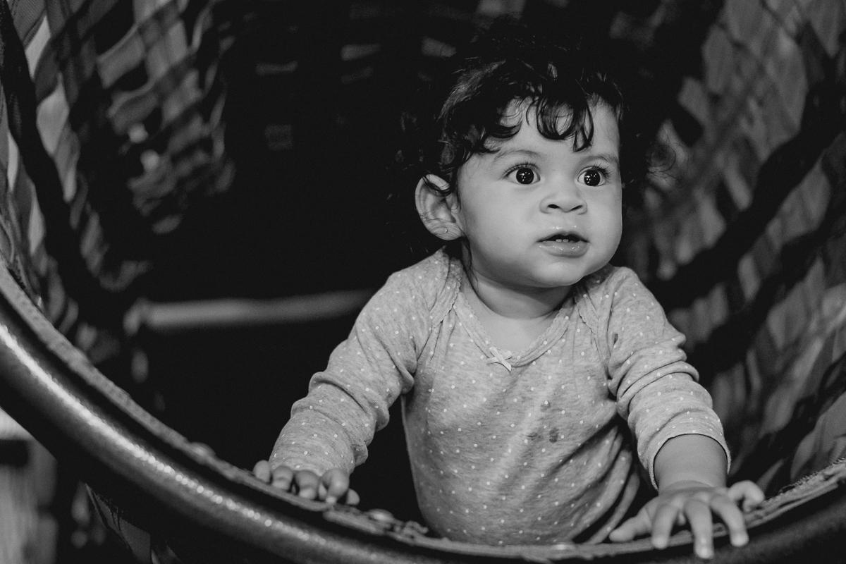 foto em preto e branco da lia brincando no tunel do brinquedao