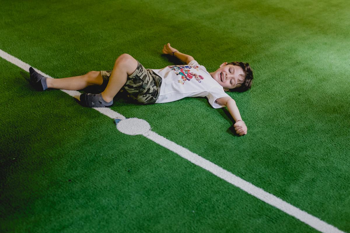 dando muitas risadas deitado no chão da quadra