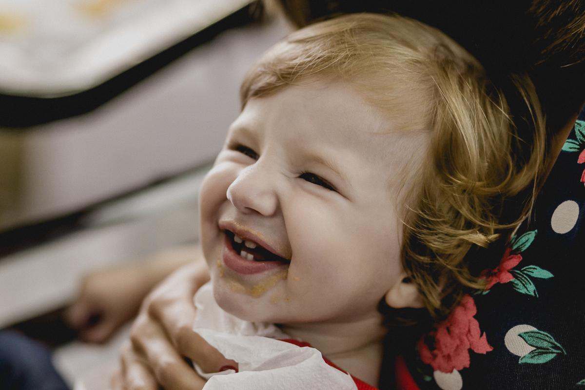 Matheus sorrindo com a boquinha suja de comida