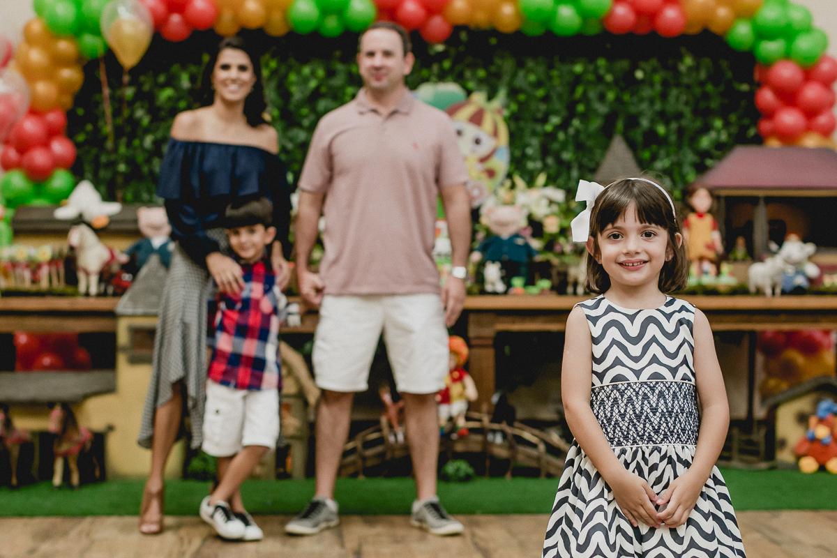 retrato em familia na frente da mesa do bolo