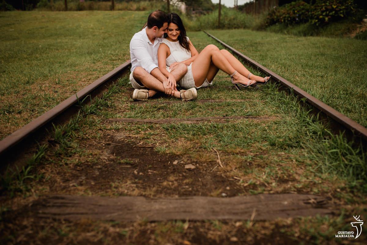 casal sentado no trilho do trem durante o book de casal em paranapiacab