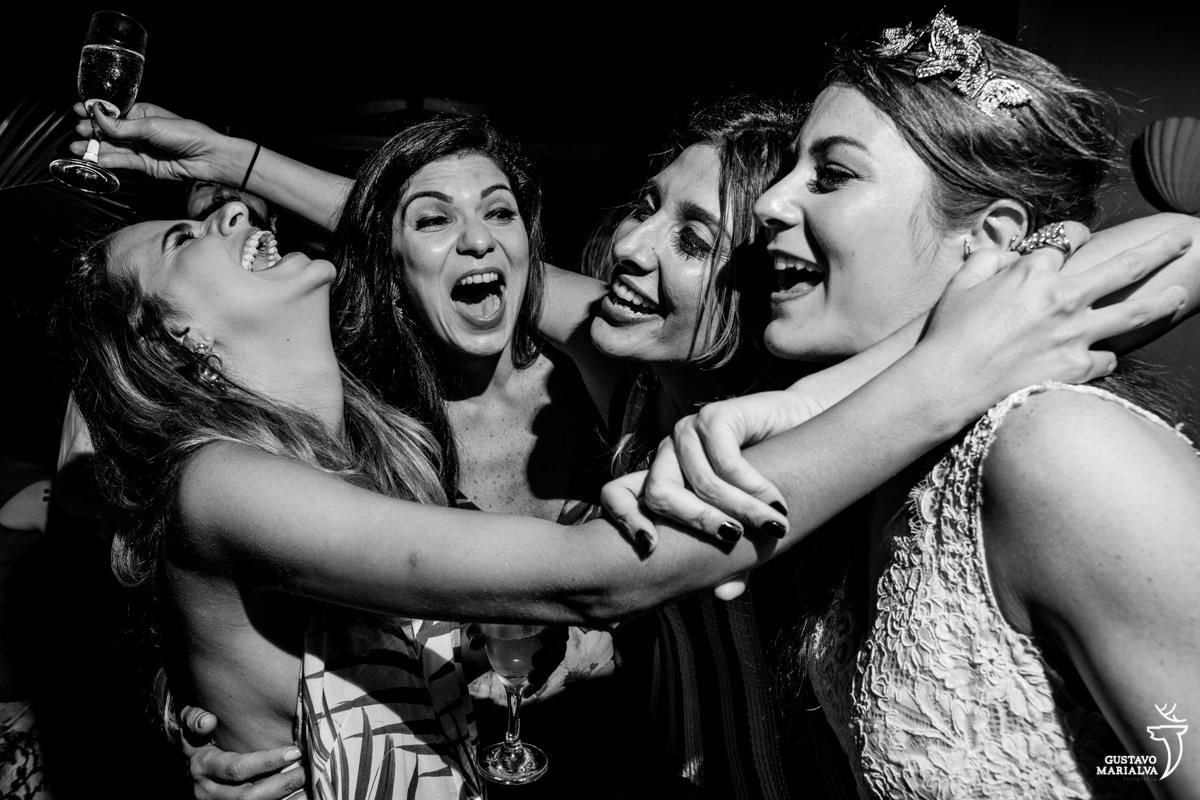 noiva e amigas sorrindo e cantando na festa de casamento