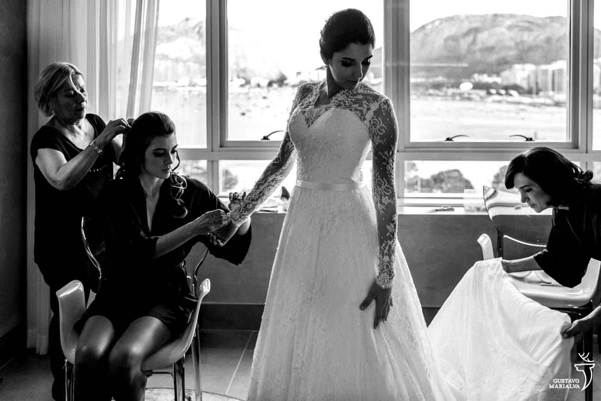 Irmã ajustado a manga do vestido da noiva e a mãe arrumando a calda