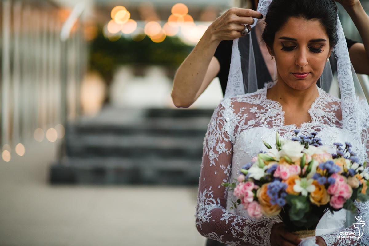 Gabi Back colocando o véu na noiva que estava segurando o buquê
