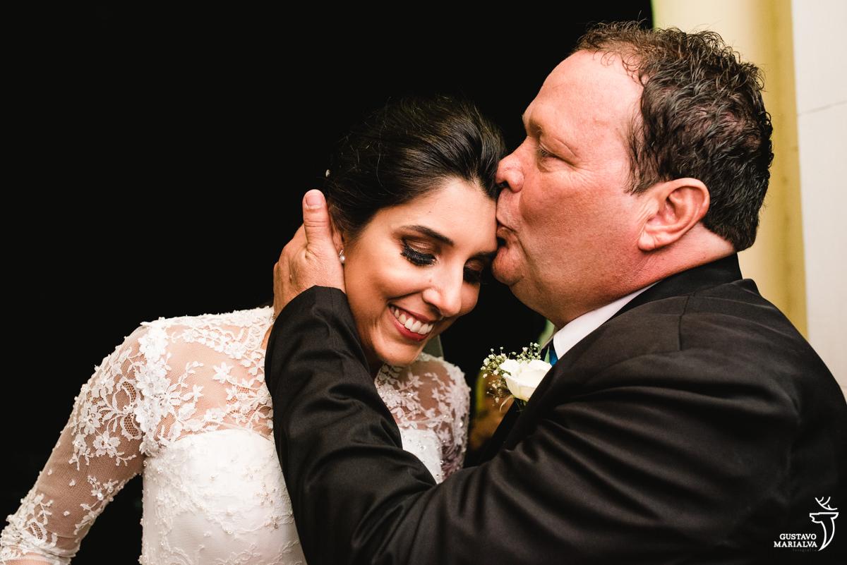 pai acalmando e beijando a testa da noiva na entrada da igreja na cerimônia de casamento