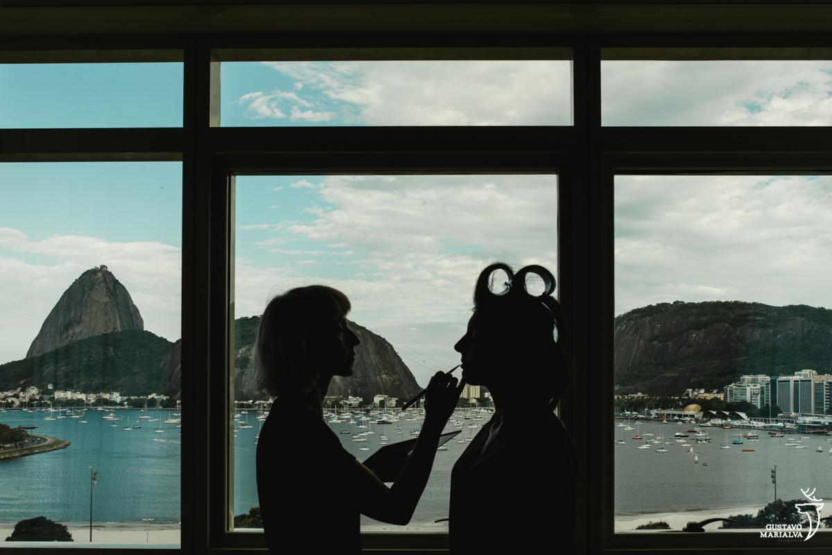 noiva sendo maquiada com o pão de açúcar de fundo no hotel Yoo2 Rio