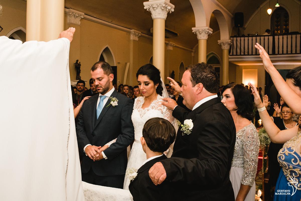 Pais e familiares abençoando os noivos na cerimônia de casamento