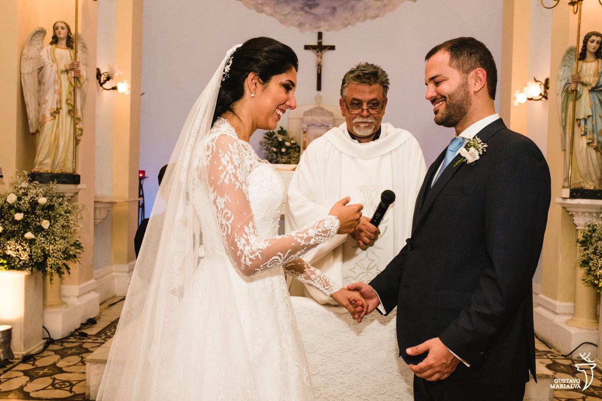 Noivos sorrindo ao trocarem votos na cerimônia de casamento