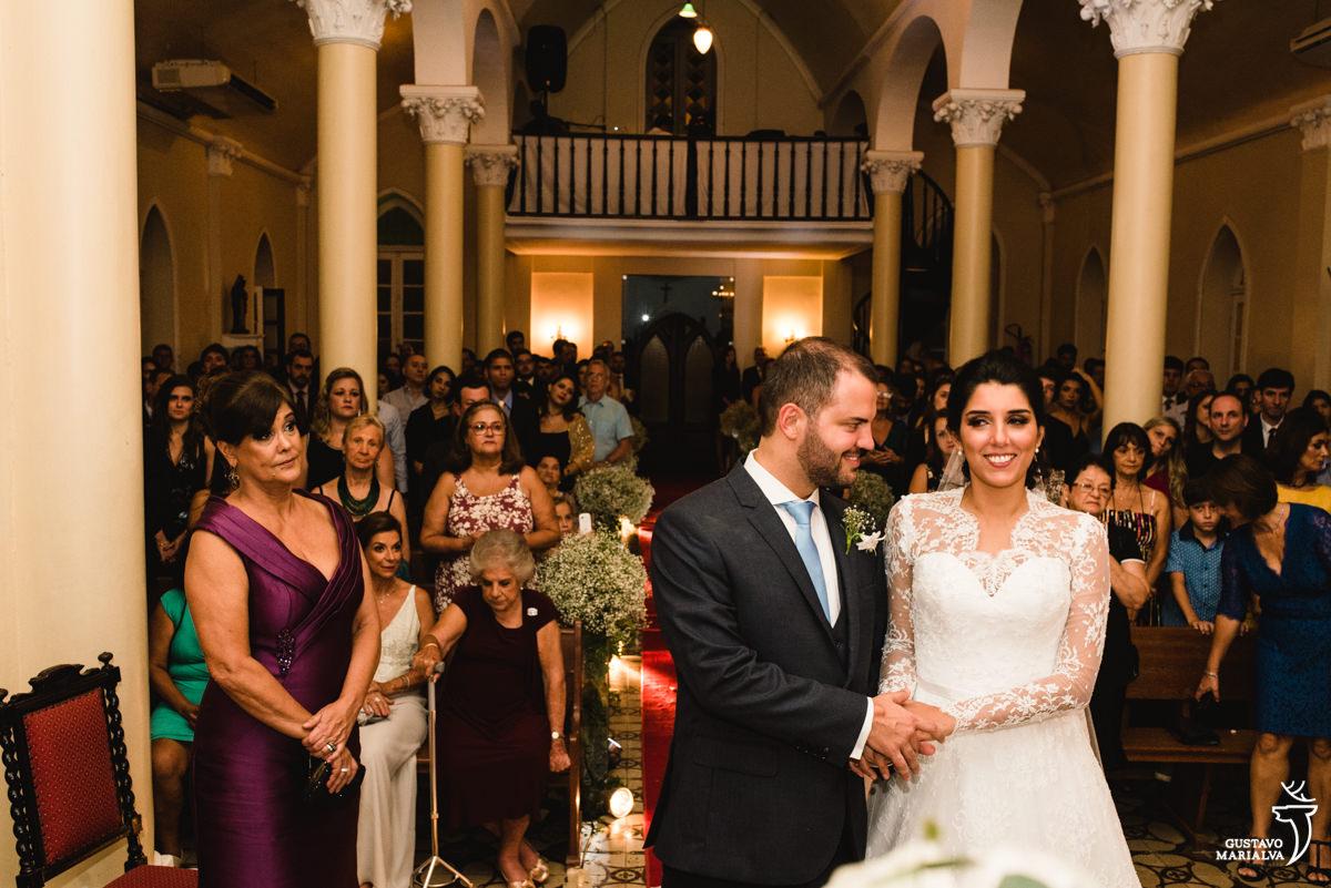 Novo fazendo carinho na noiva e sendo observado pela mãe durante a cerimônia de casamento