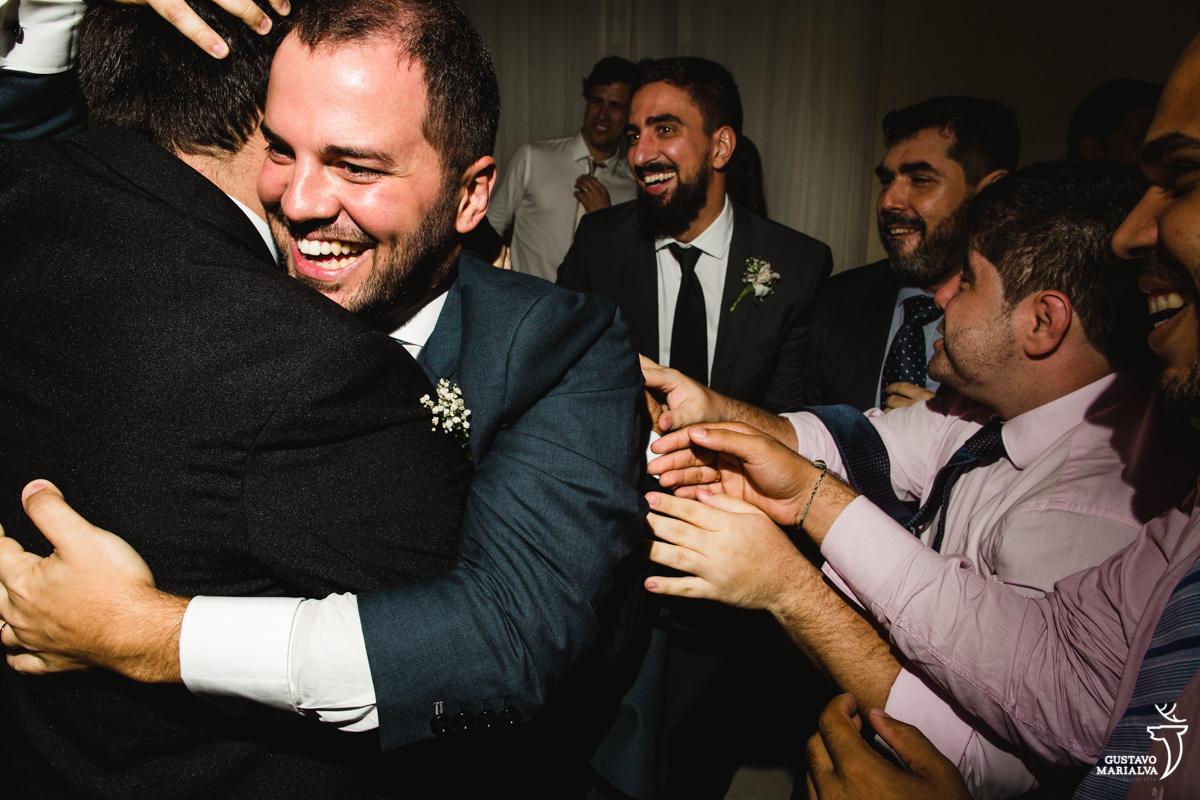 Noivo abraçando amigos e padrinhos sorrindo no fundo