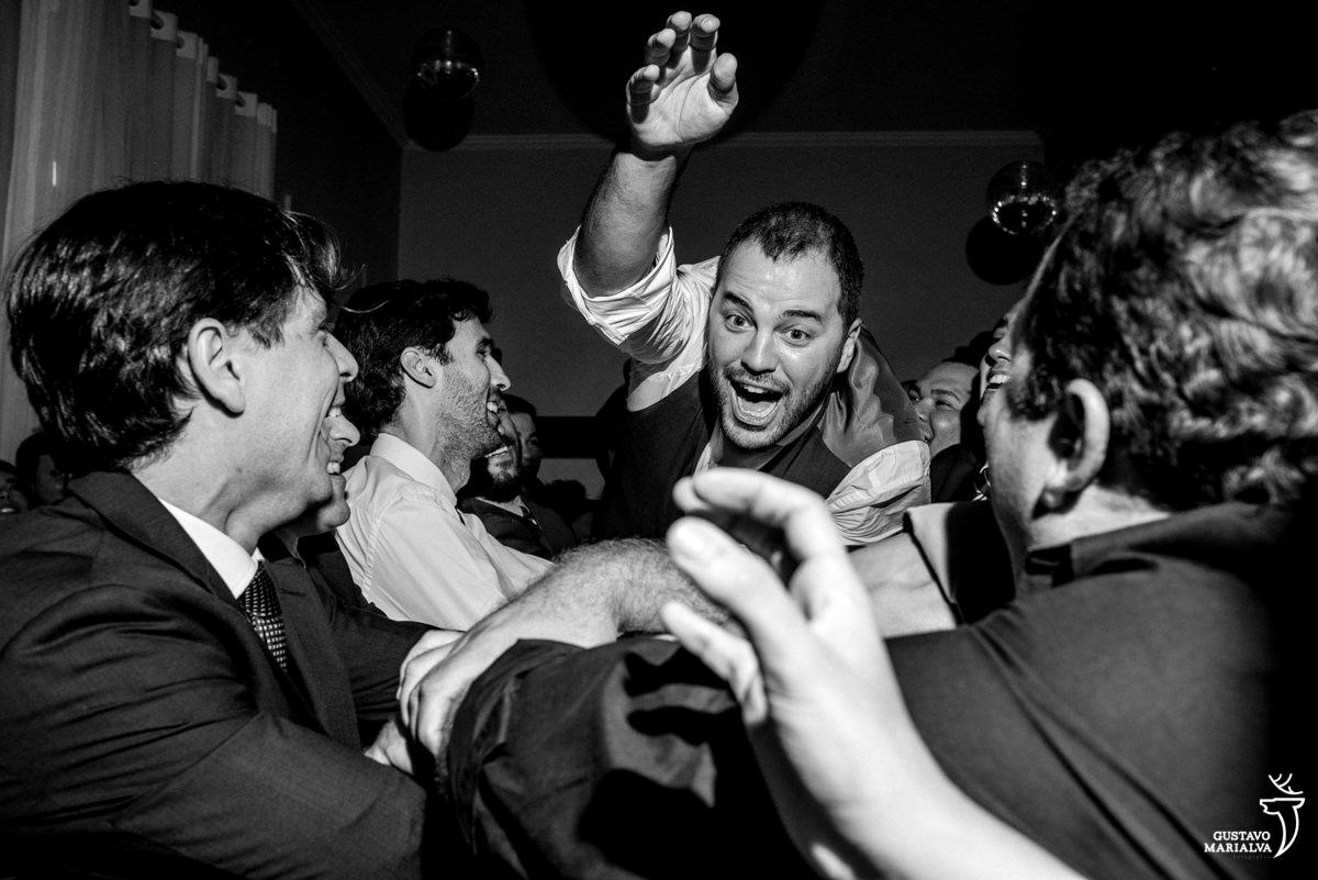 Padrinhos jogando o noivo para o alto na festa