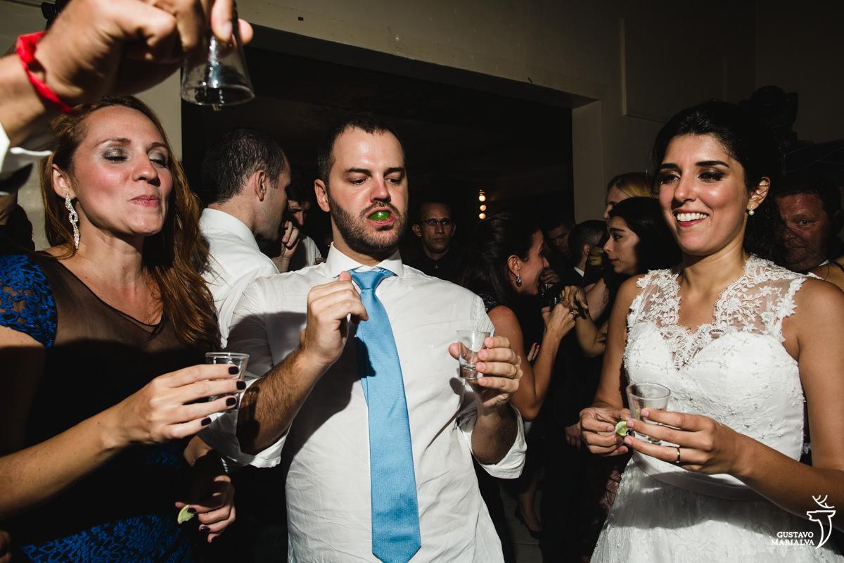 Noivo e noiva tomando tequila