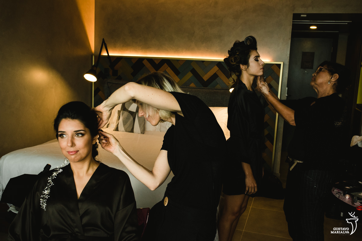 Gabi Back arrumando o cabelo da noiva e irmã se maquiando