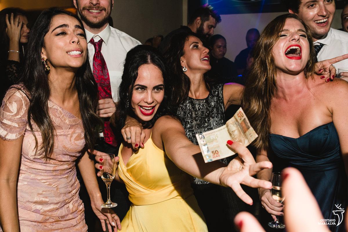 Amigo dançando e convidada mostrando uma nota de 50 reais