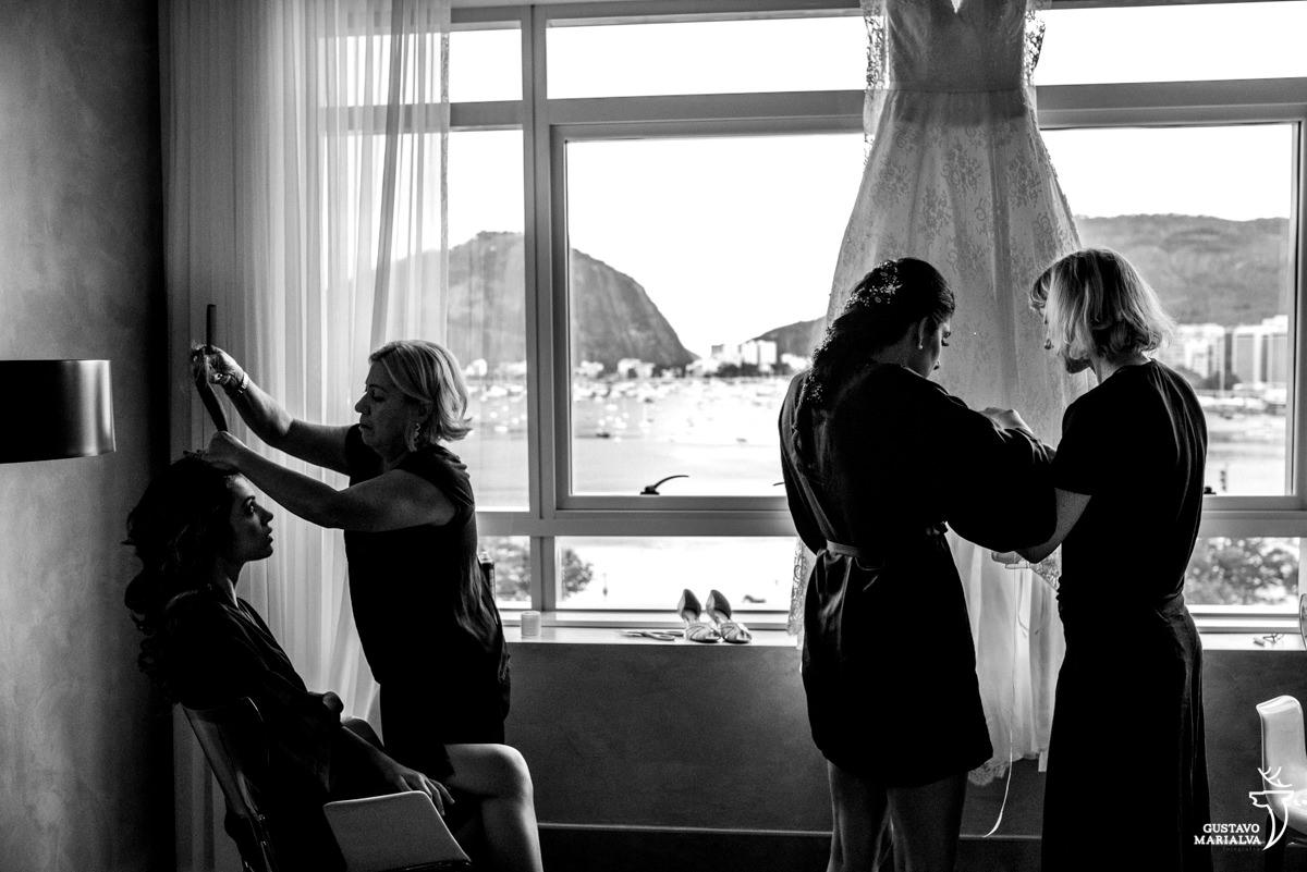 Noiva e maquiadora costurando os nomes das amigas na barra do vestido de noiva Carol Hungria
