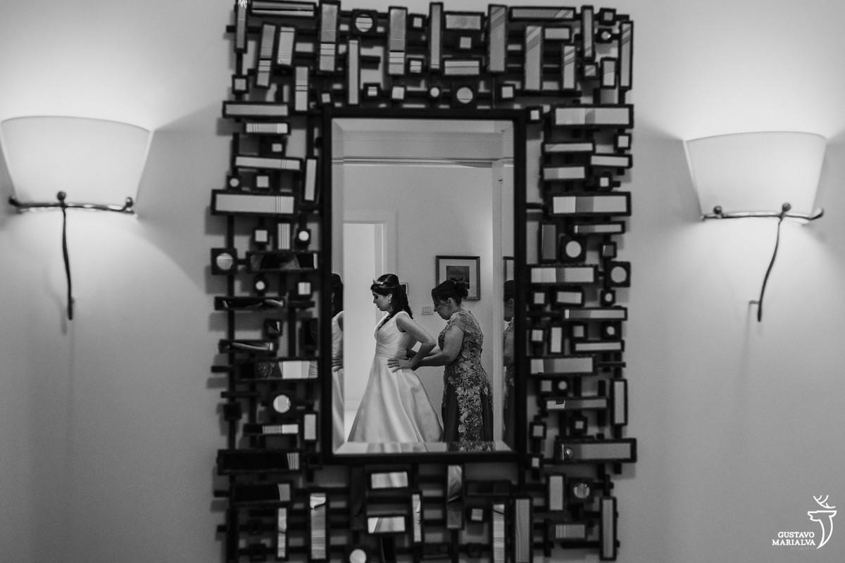 mãe da noiva fechando o vestido no reflexo do espelho na parede
