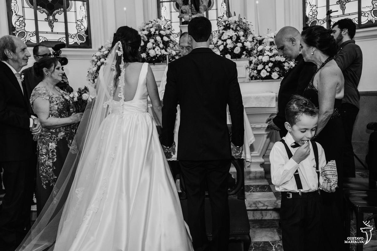 pajem comendo pipoca durante a cerimônia de casamento