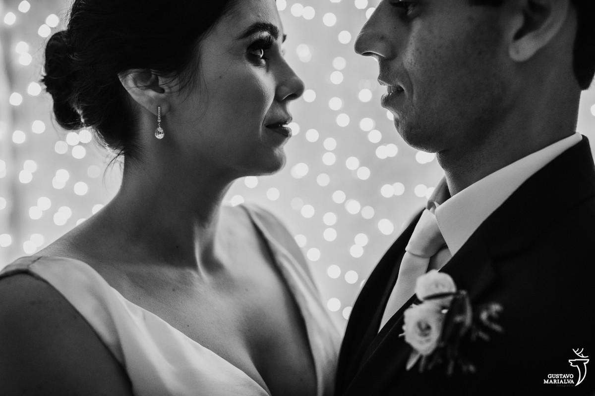 noivos se olhando apaixonados com parede de luzes de natal ao fundo