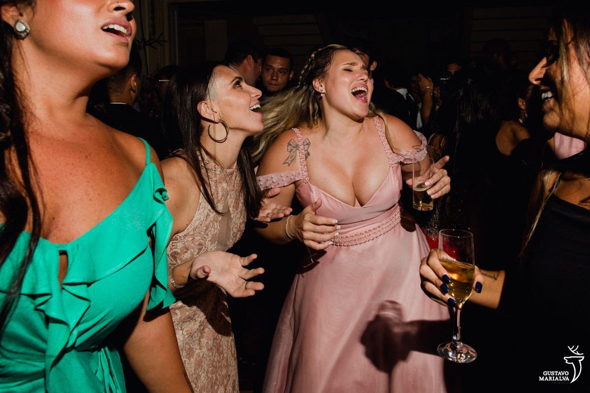amigas cantando música e segurando espumante na festa de casamento no fluminense